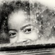Little girl from Madagascar smiles behind the window — Стоковая фотография