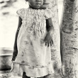 Stock Photo: Benin little girl stays near tree