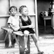 Two little Benin girls sit together on a bench — Stock Photo