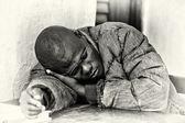 Hombre de benin duerme sobre una mesa — Foto de Stock