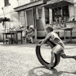 Little Ghanaian boy plays with a tire and his mother looks at him — Stock Photo