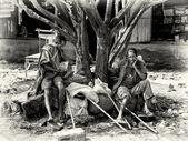 Two Ethiopian men with wooden sticks sit on the stone — Stock Photo
