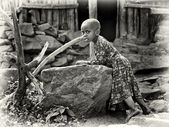 Little Ethiopian girl stays next to the stone — Stock Photo