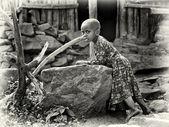 Little Ethiopian girl stays next to the stone — Stock Photo