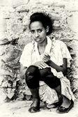 Ethiopische jongedame zit in de buurt van een stenen muur — Stockfoto