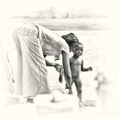 Eine ghanaerin wäscht ihr kleines baby auf der straße — Stockfoto
