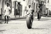 Petit garçon ghanéen traverse la rue avec un pneu — Photo