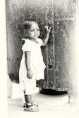 Little Ghanaian girl stays near the wall — Stock Photo
