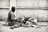 Ein ghanaischer Mann sitzt auf dem Boden mit seinen Sachen — Stockfoto