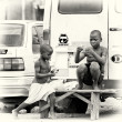 Stock Photo: Two Ghanaichildren sit on bench near road