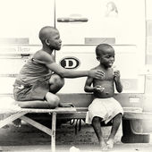 A Ghanaian boy eats something and an other boy wants to try it as well — Stock Photo