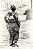 En ghanansk kvinna bär sitt barn på ryggen — Stockfoto