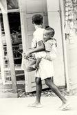 ガーナの小さな女の子は彼女の背中に彼女の弟を運ぶ — ストック写真