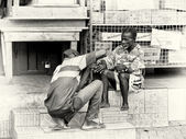 A Ghanaian man cuts the nails of an old man — Foto Stock