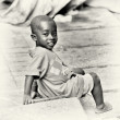 Stock Photo: Little Ghanaiboy sits on ground