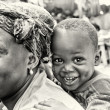 Cute smily boy from Ghana on the back of his mother — Stock Photo