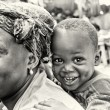 Cute smily boy from Ghanon back of his mother — Stock Photo #11961852