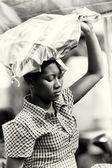 En ghanansk dam bär massa saker över huvudet — Stockfoto