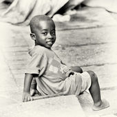 Little Ghanaian boy sits on the ground — Stock Photo