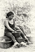 A Ghanaian woman sitls and waches the food — Foto de Stock
