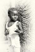 Little girl from Ghana eats something near a tree — Stock Photo