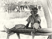 An old from Ghana sits the curious way on a wooden bench — Stock Photo