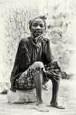 A Ghanaian lady sits on the stone — Photo