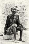 Eine ghanaische dame sitzt auf dem stein — Stockfoto