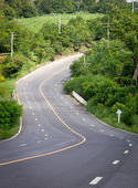 The road curves up the mountain. Line yellow and white road. — Stock Photo