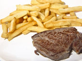 A sirloin with fried potatoes — Stock Photo