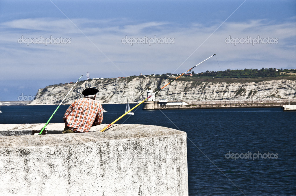 A fisherman in a port with two rods — Stock Photo #11830551
