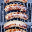 Five delicious brats on the grill — Stock Photo