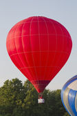 Red Hot Air Balloon lifting off — Stock Photo