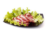 Close-up of cold sliced on a black plate isolated on white — Stock Photo