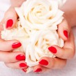 Closeup image of red manicure with flowers - Stock Photo