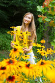 Portrait of a young woman close up in the woods with flowers — Stock Photo