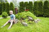 Boy among flowers and other plants — Stock Photo