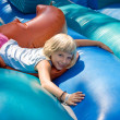 Girl playing on an inflatable toy - Stock Photo