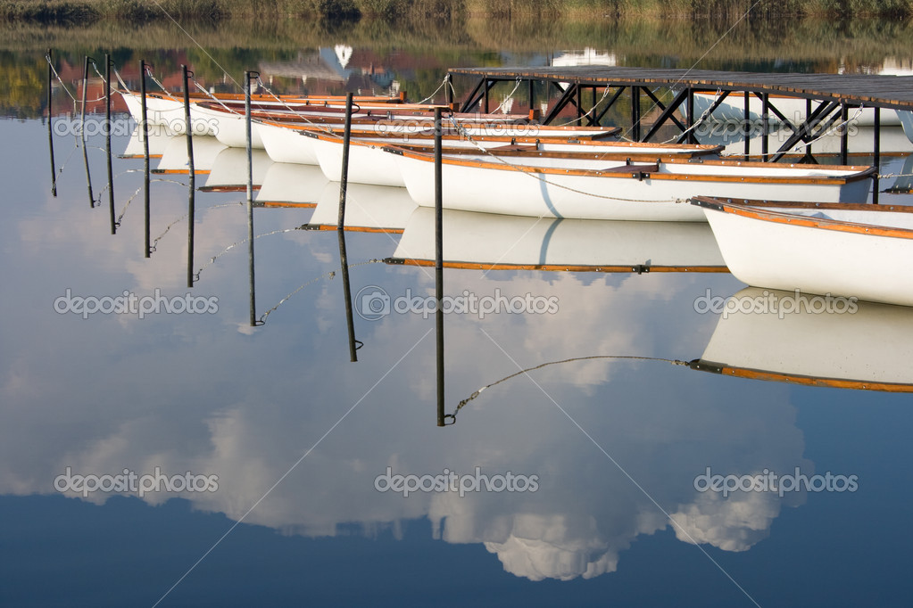 Water mirroring white boats and the cloudy sky.  Stock Photo #11678088