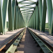 Train bridge with green painted steel pillars and tracks. — Stock Photo