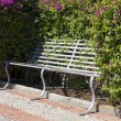 Bench with flowering shrub - Stock Photo