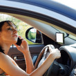 Woman driver using mobile phone - Stock Photo