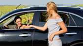 Woman talking to female driver in car — Stock Photo