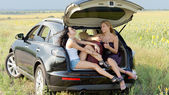 Mulheres relaxantes no porta malas do carro — Fotografia Stock