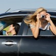 Woman leaning out of car photographing — Stock Photo