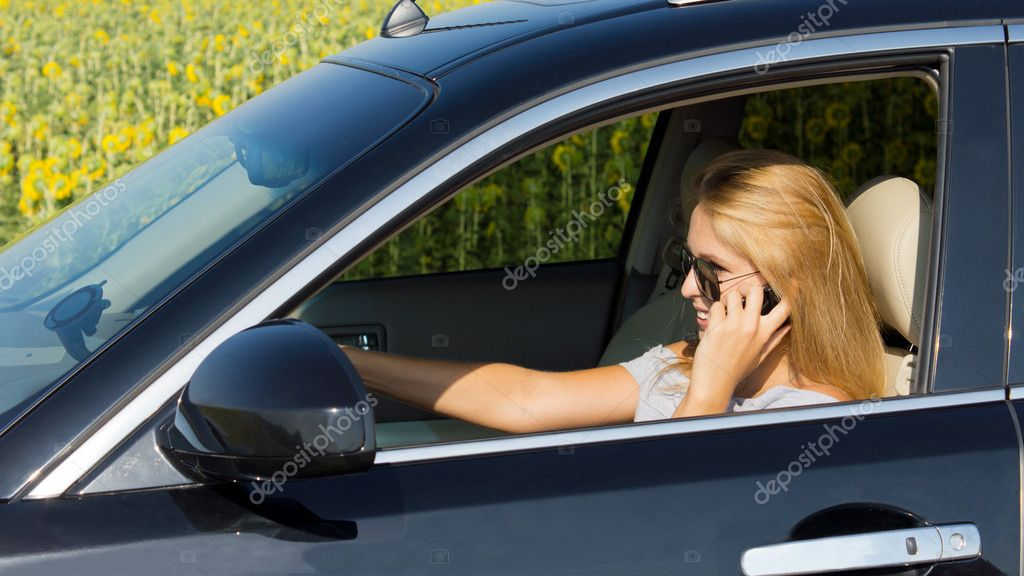 Woman driver talking on her mobile phone with her car safely pulled over to the side of the road near a field of sunflowers — Stock Photo #11950864