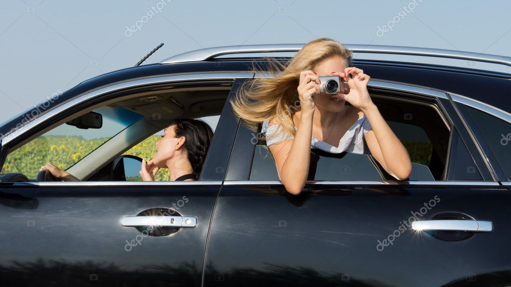 Woman leaning out of the window of a car photographing with a compact digital camera  Stock Photo #11950890