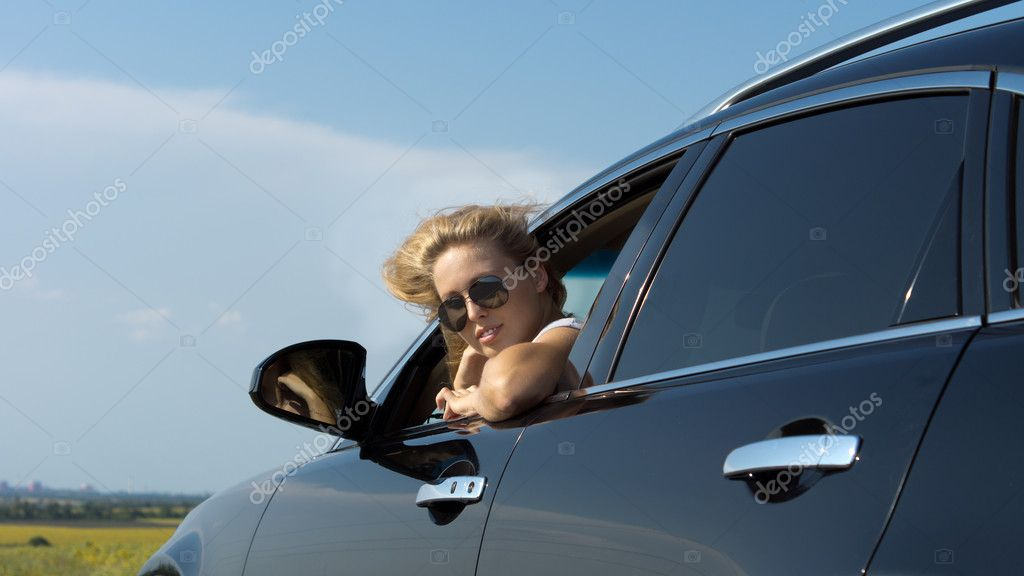 Low angle view of a blonde woman in sunglasses looking back out of a car window — Stock Photo #11950908