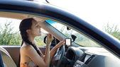 Female driver applying make-up — Stock Photo