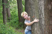 The girl the blonde covers a tree — Stock Photo